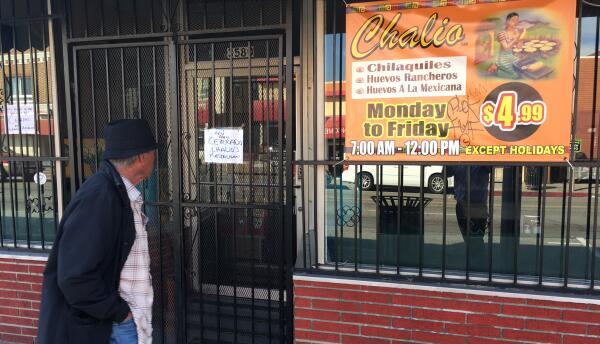Un peatón pasa delante de un restaurante mexicano en Los Ángeles que cer...