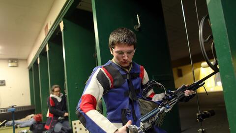 Un joven revisa su arma durante una competencia de tiro en Connecticut e...