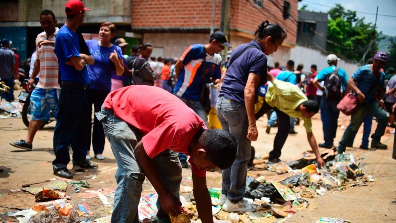 Los residentes de El Valle, en Caracas, buscan comida entre los restos q...