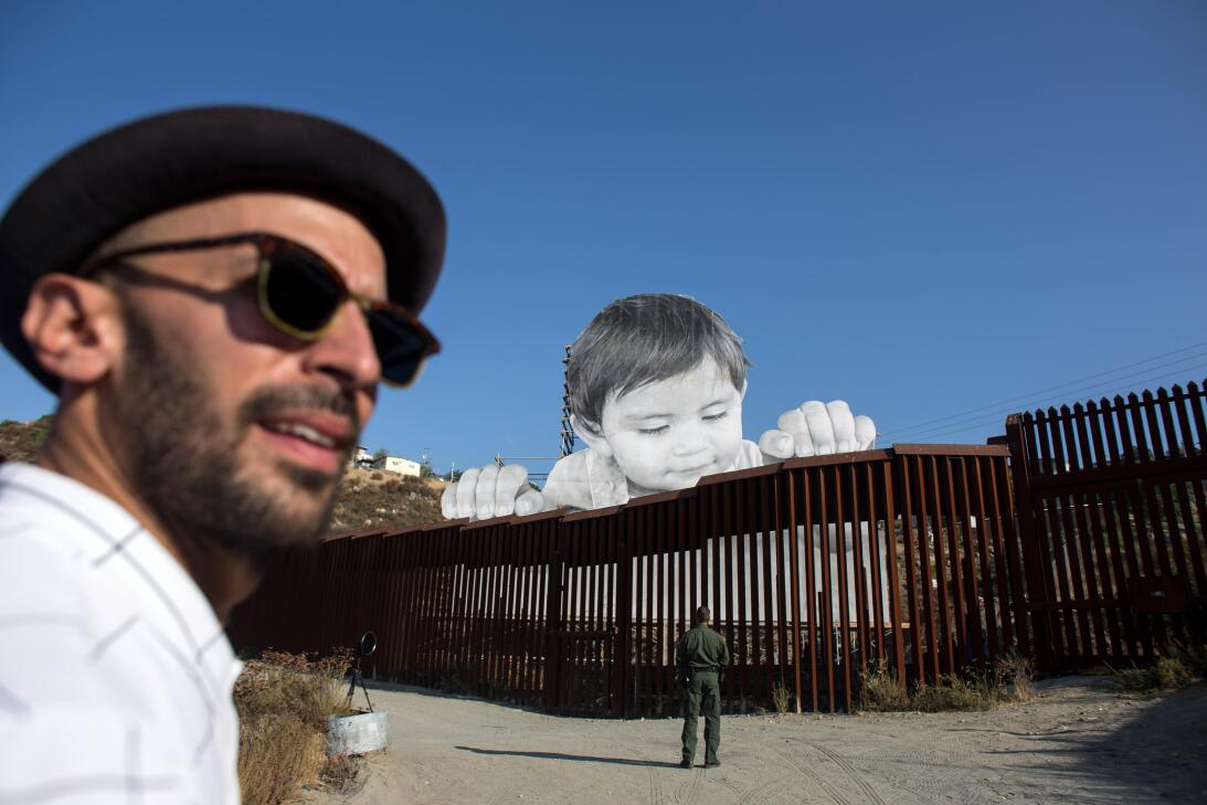 What is this curious child thinking as he peers over the border wall? Ge...
