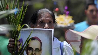Una mujer con una imagen de Órcar Romero durante una marcha en San Salva...