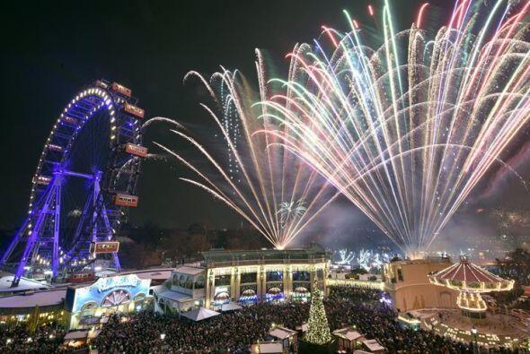 La gigante rueda Vianesa fue iluminada mientras fuegos artificiales esta...