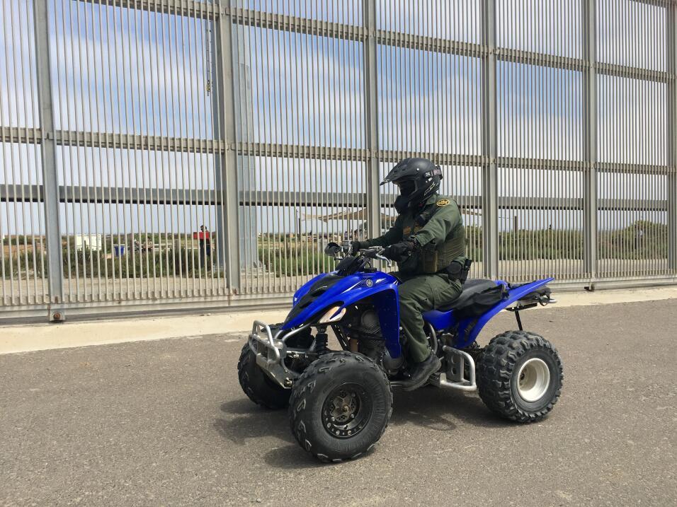 Un agente fronterizo en cuatrimoto patrulla cerca de la playa de San Diego.