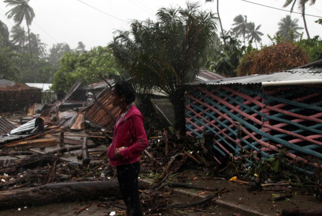 Una mujer contempla bajo la lluvia la destrucción de construcciones en N...