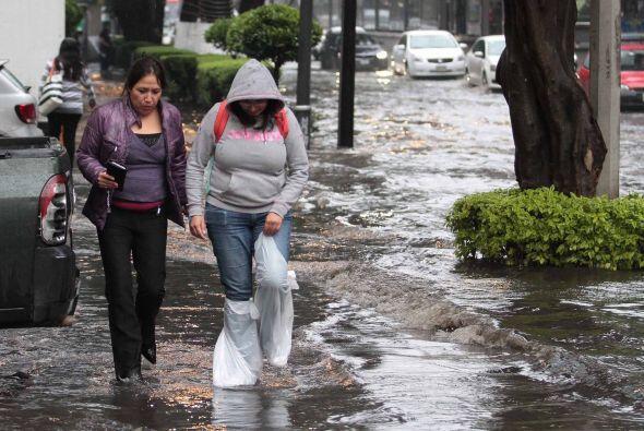 Dos mujeres tratan de pasar sobre una calle inundada del centro de la ca...