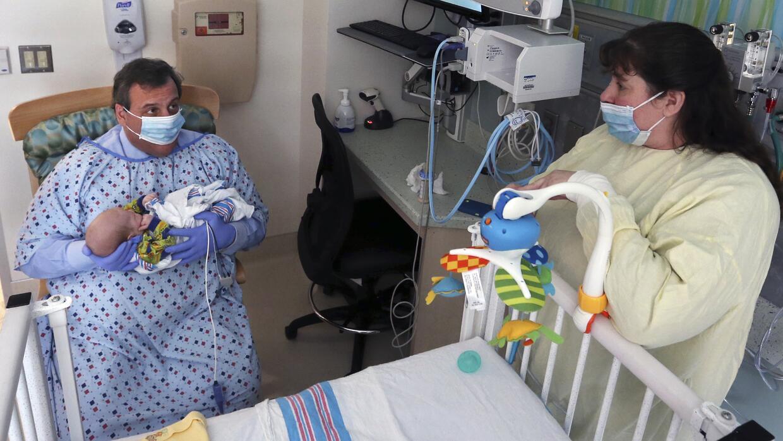El gobernador de Nueva Jersey Chris Christie sostiene a un bebé que está...