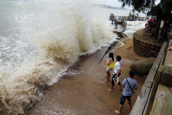 Un grupo de visitantes chinos frente a las fuertes olas que golpean la c...