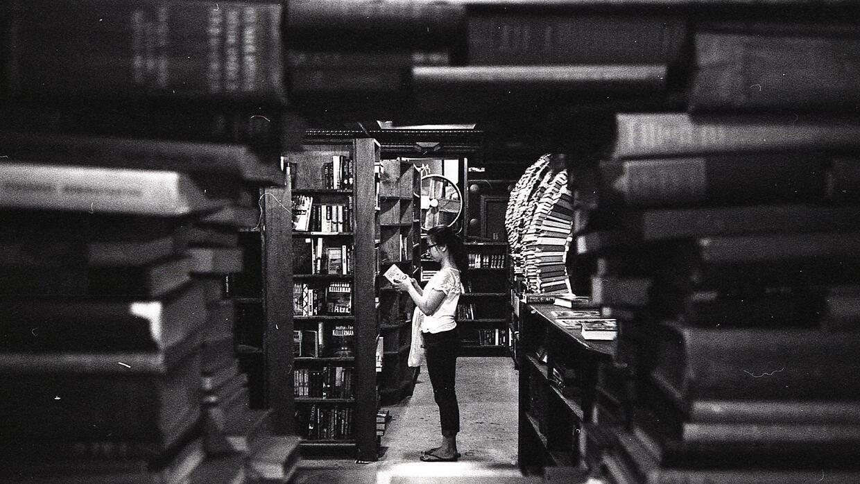 Un cliente ojeando un libro en The Last Bookstore.