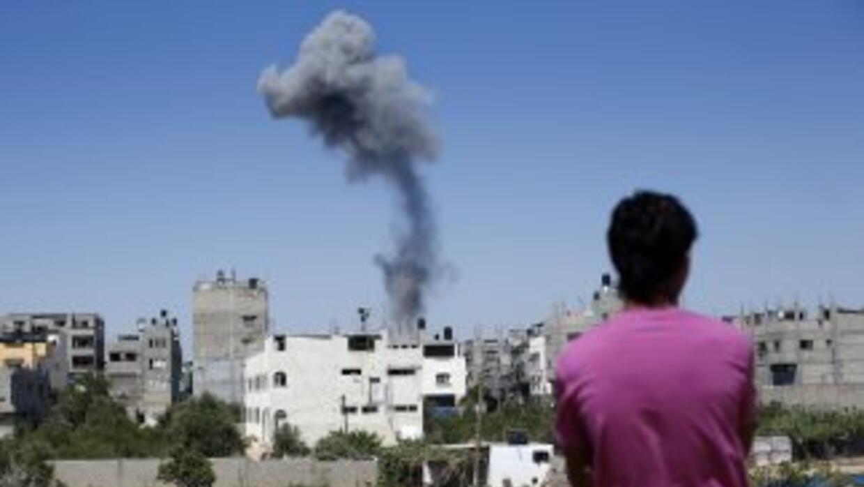 Un palestino mira el humo que sale de un edificio tras un ataque aéreo e...