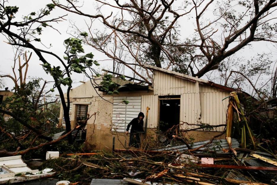 Un hombre busca sus pertenecias en una vivienda destruida por María en G...