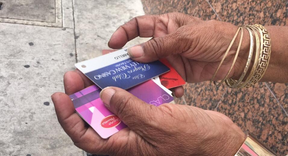 Una anciana latina muestra tarjetas de casinos del sur de California que...
