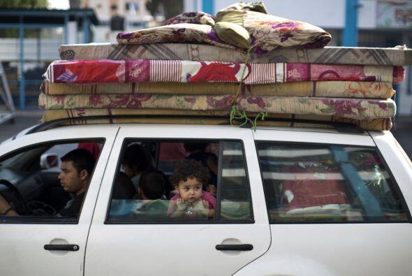 Una familia regresa a su casa con sus pertenencias en la   ciudad de   B...