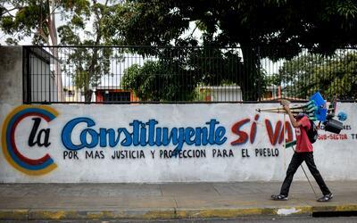 Un vendedor ambulante camina frente a un mural que promociona la Asamble...