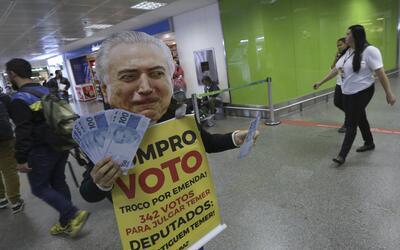 Un activista protesta, con una máscara del presidente de Brasil,...