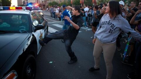 Un hombre patea una patrulla durante los disturbios por las muertes a ti...