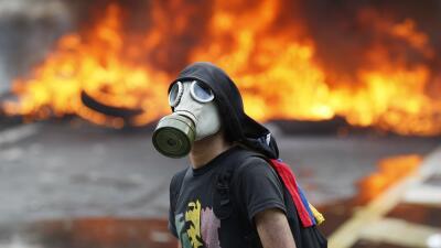 Un manifestante contra el gobierno de Nicolás Maduro en una carretera en...