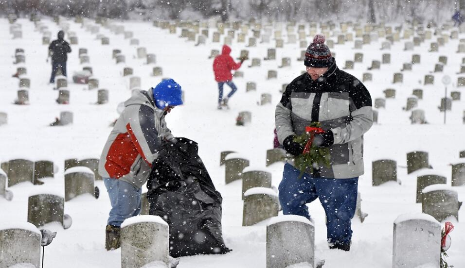Dos personas colacan coronas en un cementerio de soldados en Erie.