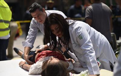 Una mujer herida durante el sismo es asistida por paramédicos en...