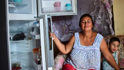 Liliana Rojas muestra su nevera vacía en el barrio caraqueño de Catia.