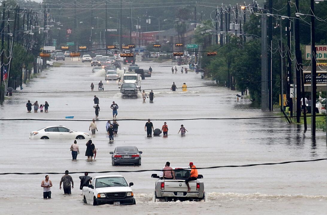 Residentes atraviesan un rio que se formó sobre la calle Telephone Rd. M...