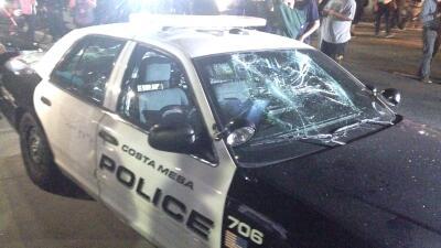 Auto de policía con los vidrios rotos en un mitin de Trump en Costa Mesa