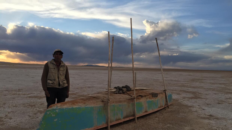 Valerio Rojas, pescador del lago Poopó, junto a la barca con la que trab...