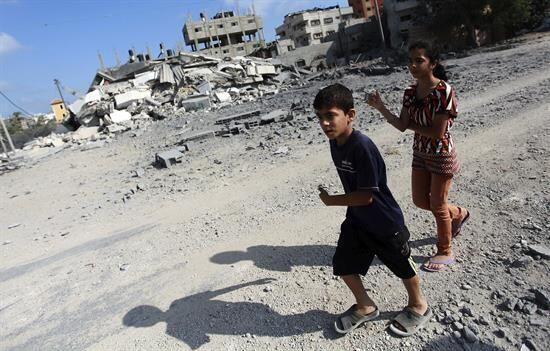 Niños corren ante la devastación.