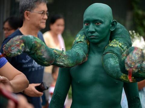 Un hombre con una serpiente de dos cabezas y con el cuerpo pintado de co...