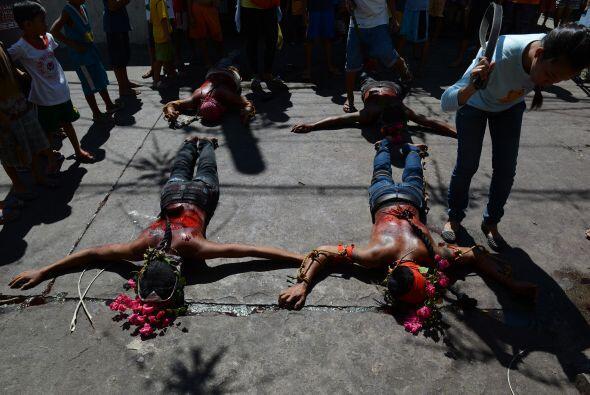 Una mujer, usando una fusta, flagela a los penitentes que participan en...