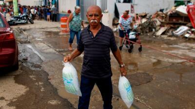 Horas de fila para conseguir dos bolsas de hielo en Arecibo, Puerto Rico.