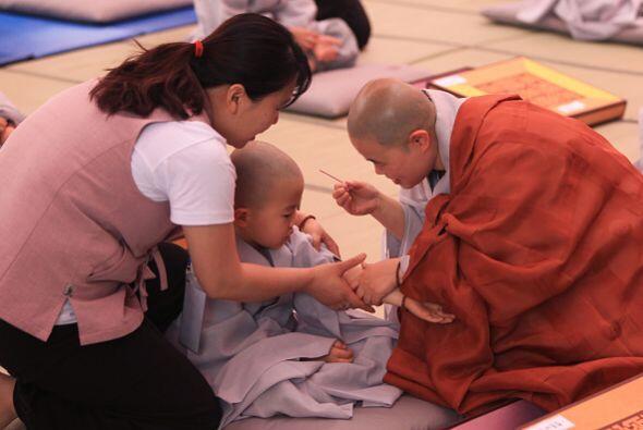 Un monje se acerca a  un niño para ponerle un tipo de incienso en su brazo.