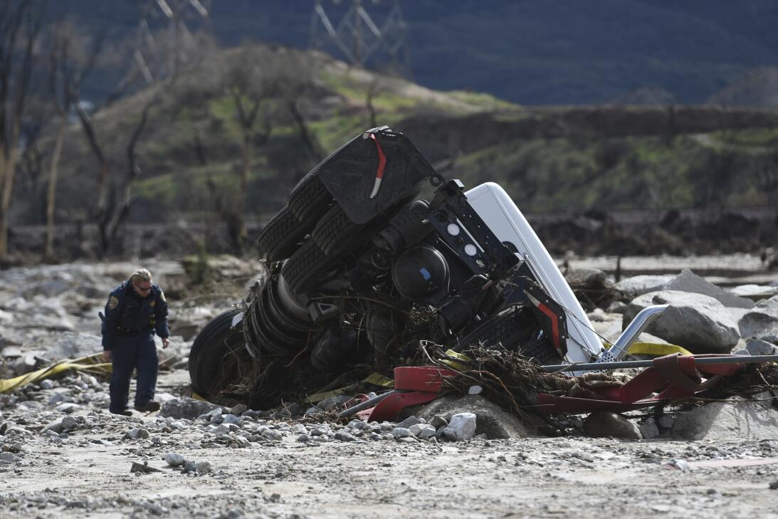 Un funcionario revisa un camión de carga que se volteó luego que colapsa...
