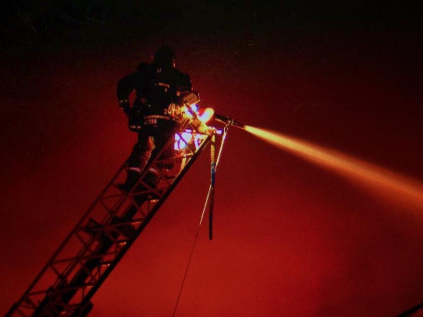 Un bombero trabaja en altura para echar agua dentro del almacén en llamas