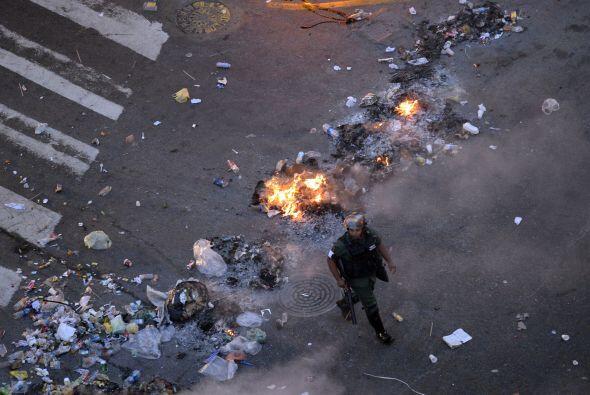 Un miembro de la Guardia Nacional camina al lado del fuego.  Los estudia...
