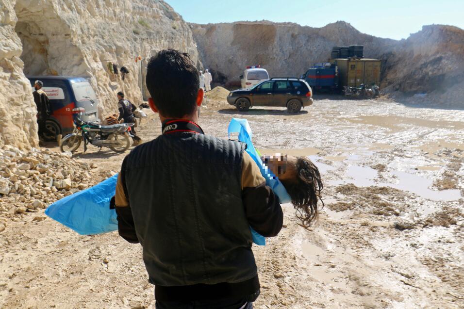 Un rescatista lleva el cuerpo de un niño que murió a consecuencia de la...