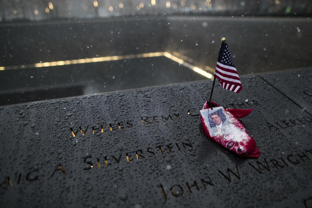 Snow falls on an American flag and portrait of a victim of the September...