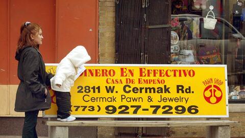 Una mujer hispana y su hija caminan junto a un banco en Little Village,...