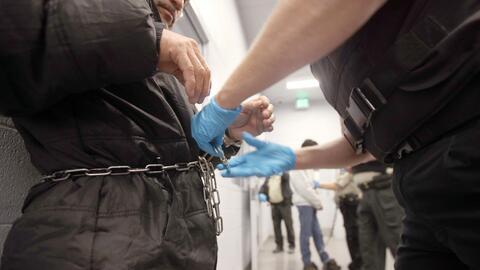 Un agente federal encadena a un inmigrante indocumentado a punto de ser...