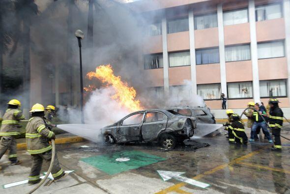 En las afueras del Congreso, decenas de bomberos trabajaban en extinguir...