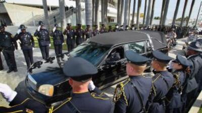Los policías en asistencia al memorial le dan un saludo oficial a la car...