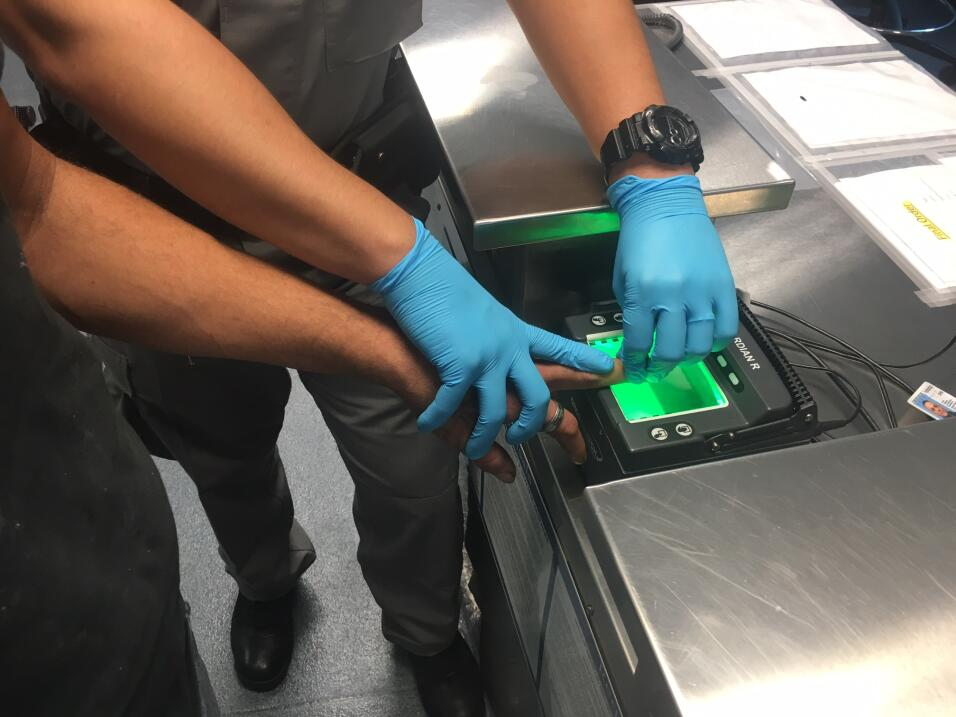 Toma de huellas digitales de uno de los inmigrantes bajo custodia.