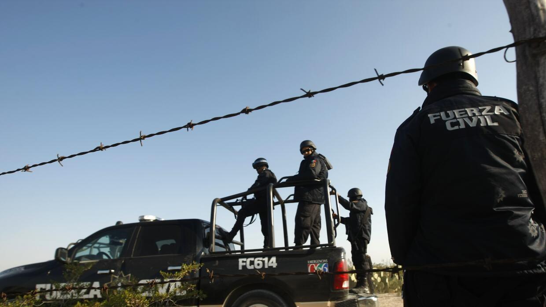 Policías mexicanos reguardan el lugar del crimen contra una persona en e...