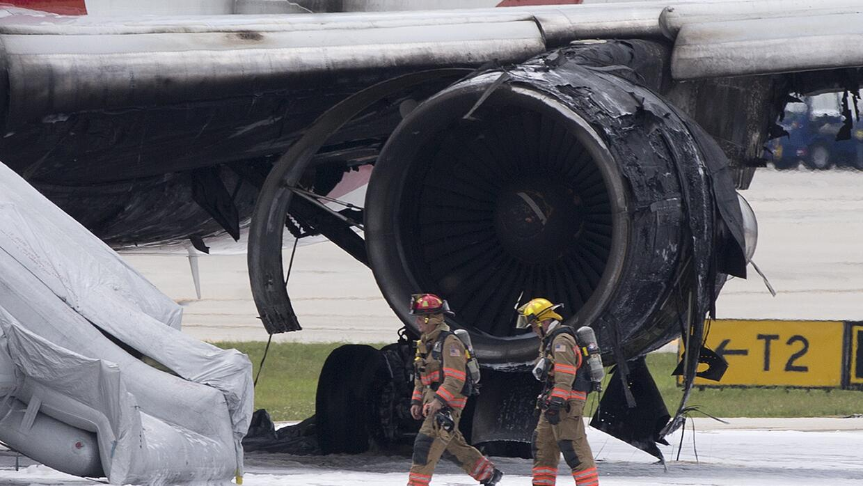Un par de bomberos caminan junto a una turbina quemada de un Boeing 767...