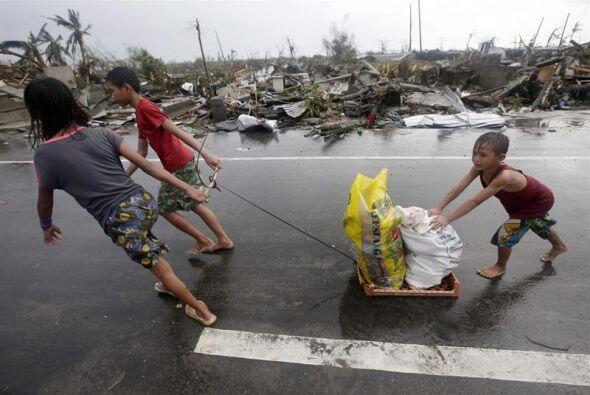 Niños de Filipinas arrastran sacos con objetos recuperados en medio de l...