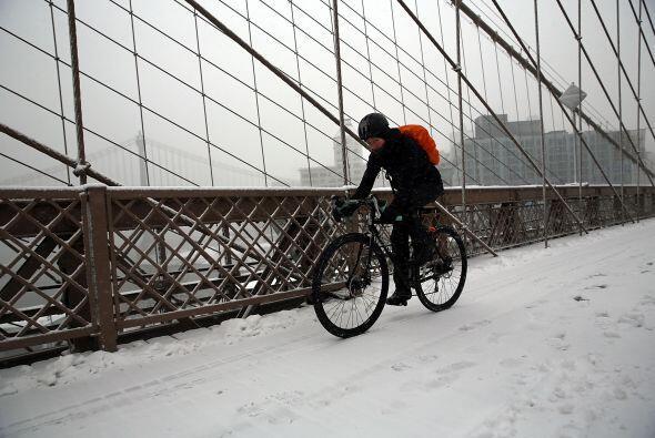 Un ciclista se esfuerza en recorrer el puente de Brooklyn debido a la ni...