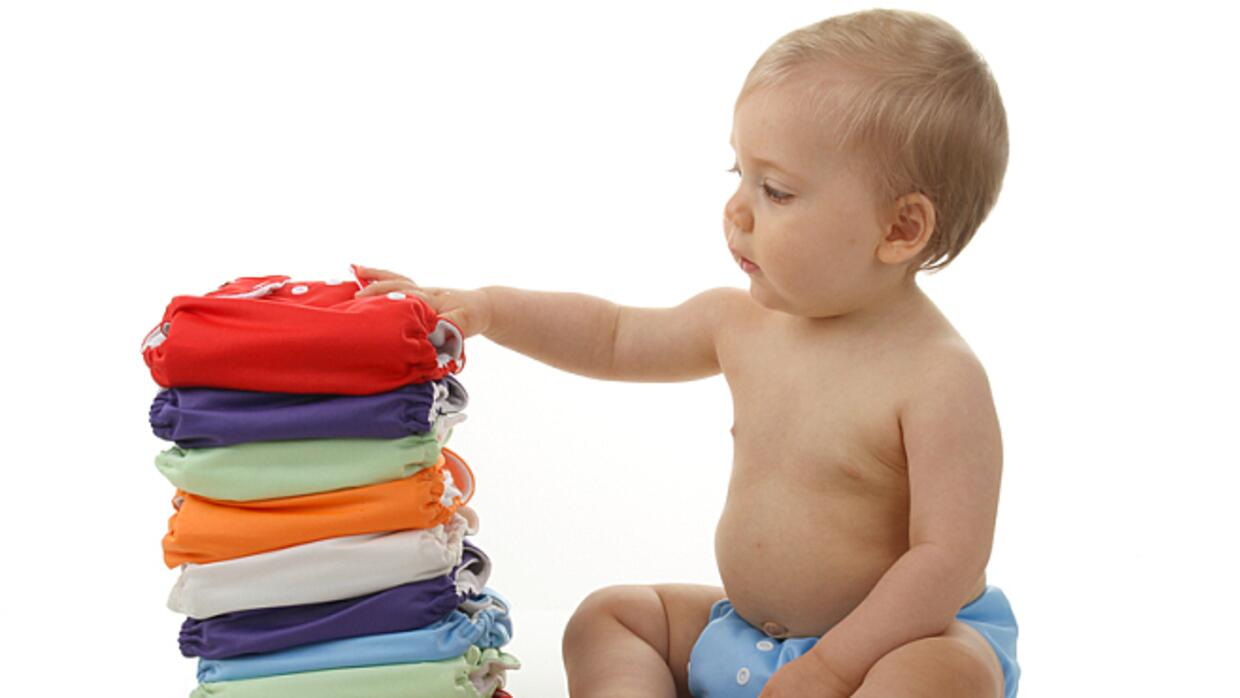 Baby with a stack of cloth diapers