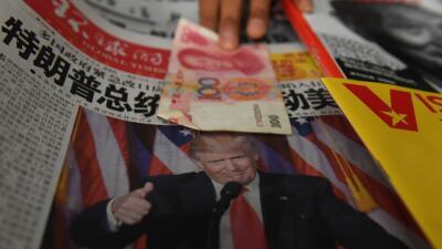 Un billete de 100 yuanes sobre un periódico en Pekín con la imagen del p...