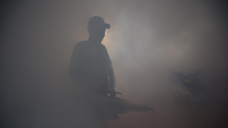 Un trabajador del ministerio de Salud fumiga en un de Guatemala.