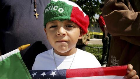 Un niño sostiene una bandera de EEUU en una marcha de 2006 en National C...