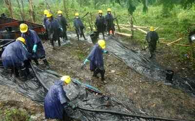 Trabajadores limpian un derrame de petróleo este martes, 9 de febrero de...